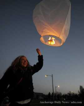 Claire releases a lantern in honor of Domestic Violence Awareness Month