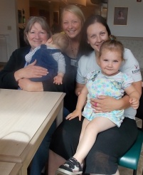 Beth (in the middle) poses with a mother (on right), her two young children, and her doula mentor